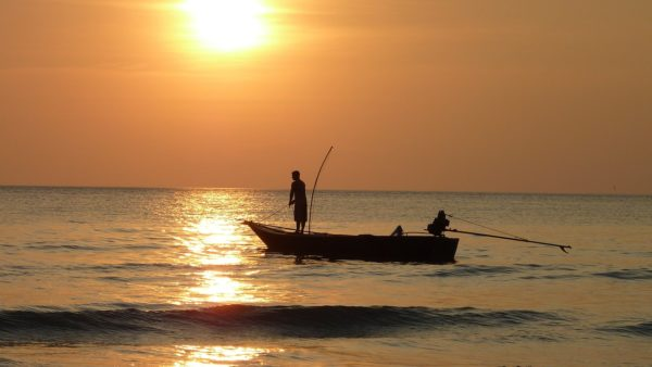 Fisher on a boat at sunset